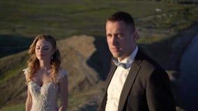 Νύφη και νεόνυμφος που περπατούν στο βουνό στο ηλιοβασίλεμα φιλμ μικρού μήκους