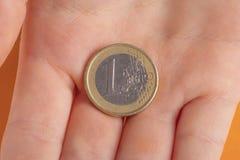 Νόμισμα 1 ευρώ στο χέρι ενός εφήβου παιδιών σε ένα πορτοκαλί υπόβαθρο στοκ φωτογραφίες