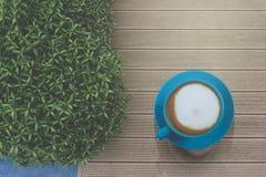 Νόστιμη κατανάλωση, μπλε φλυτζάνι του καφέ cappuccino, γάλα σχεδίων λουλουδιών εμπρός στον εκλεκτής ποιότητας ξύλινο πίνακα και ο στοκ εικόνες