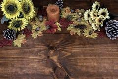 Ντεκόρ ημέρας των ευχαριστιών με το κερί, τους παγωμένους κώνους πεύκων, τους ηλίανθους, τα βελανίδια και τα φύλλα σφενδάμου στοκ φωτογραφία