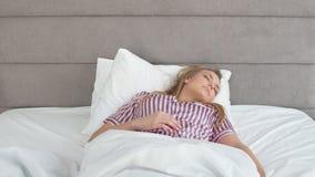 ξένοιαστη ζωή Όμορφο κορίτσι που ξυπνά στο κρεβάτι το πρωί φιλμ μικρού μήκους