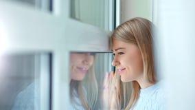 Ξένοιαστη χαμογελώντας νέα γυναίκα κινηματογραφήσεων σε πρώτο πλάνο που κοιτάζει στο παράθυρο σχετικά με το γυαλί με το χέρι την  φιλμ μικρού μήκους
