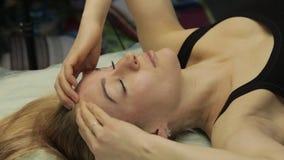 Ξανθή γυναίκα που κάνει το του προσώπου μόνος-μασάζ αντι-γήρανσης ασκήσεις για το αντι κρεμώντας δέρμα απόθεμα βίντεο