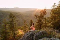 Ξανθή συνεδρίαση τουριστών γυναικών σε έναν βράχο στα βουνά κάτω από το ηλιοβασίλεμα το καλοκαίρι στοκ εικόνες