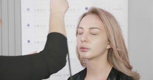 Ξανθός καλλιτέχνης makeup που χρησιμοποιεί ένα airbrush για να καλύψει τις ατέλειες δερμάτων απόθεμα βίντεο