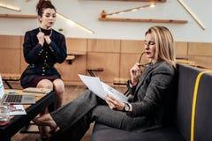 Ξανθός-μαλλιαρή επιχειρηματίας που μελετά το βιογραφικό σημείωμα του μελλοντικού γραμματέα της στοκ εικόνα