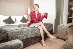 Ξανθός-μαλλιαρή συνεδρίαση επιχειρηματιών στο μεγάλο comfy κρεβάτι στο ξενοδοχείο στοκ φωτογραφίες