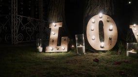 Ξύλινες επιστολές με τα φω'τα βολβών Λέξη - αγάπη Φωτισμένη ΑΓΑΠΗ λέξης στο στάδιο Αγάπη λέξης που αποτελείται από τα φω'τα επάνω φιλμ μικρού μήκους
