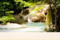 Ξύλινη επιτραπέζια κορυφή στον καταρράκτη που κρύβεται στην τροπική ζούγκλα στοκ εικόνα