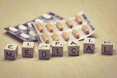 Ξύλινοι κύβοι που παρουσιάζουν τη λέξη ιατρική, χάπια στο υπόβαθρο στοκ εικόνες