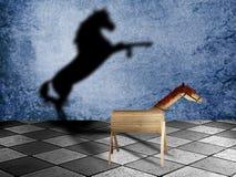 Ξύλινο άλογο παιχνιδιών με τη σκιά ως άγριο άλογο στη σκακιέρα Έννοια δυνατότητας ελεύθερη απεικόνιση δικαιώματος