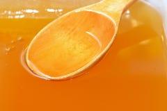 Ξύλινο κουτάλι στο φρέσκο υγρό μέλι στοκ φωτογραφία