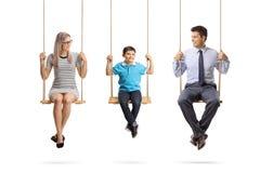 Οικογένεια μιας συνεδρίασης μητέρων, πατέρων και γιων στην ταλάντευση στοκ εικόνες