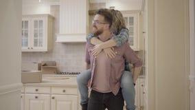 Οικογένεια που κινείται ευτυχής προς το νέο σπίτι τους Ένας χαρούμενος σύζυγος φορά μια χαμογελώντας ικανοποιημένη σύζυγο γύρω απ απόθεμα βίντεο