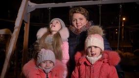 Οικογενειακό πορτρέτο καυκάσιας μητέρας και τριών κορών που τρώνε το χιόνι και που προσέχουν στη κάμερα smilingly στο βράδυ απόθεμα βίντεο
