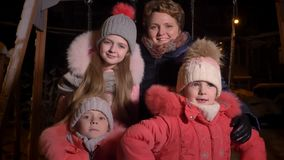 Οικογενειακό πορτρέτο καυκάσιας μητέρας και τριών κορών που τρώνε το χιόνι και που προσέχουν στη κάμερα ευτυχώς στην πόλη βραδιού φιλμ μικρού μήκους