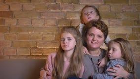 Οικογενειακό πορτρέτο καυκάσιας μητέρας και τριών κορών που αγκαλιάζουν και που προσέχουν στη κάμερα χαρωπά στο άνετο σπίτι απόθεμα βίντεο