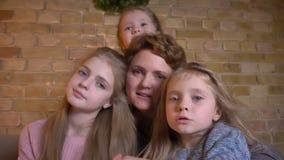Οικογενειακό πορτρέτο καυκάσιας μητέρας και τριών κορών που αγκαλιάζουν και που προσέχουν στη κάμερα smilingly στο άνετο σπίτι απόθεμα βίντεο
