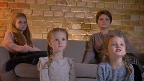 Οικογενειακό πορτρέτο της καυκάσιας μητέρας με τρεις κόρες που κάθονται μαζί και του κινηματογράφου προσοχής προσεκτικά στο άνετο απόθεμα βίντεο