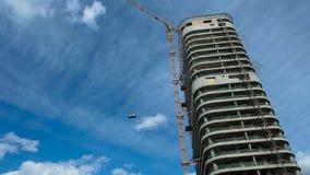 Οικοδόμηση ενός σπιτιού πολυόροφων κτιρίων κάτω από τον ουρανό, εργασία του γερανού κατασκευής, κτηματομεσιτική αγορά, διάστημα α απόθεμα βίντεο