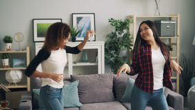 Οι αρκετά νέες γυναίκες Ασιάτης και ο αφροαμερικάνος χορεύουν στο σπίτι ακούοντας τη μουσική και έχοντας τη διασκέδαση που χαλαρώ φιλμ μικρού μήκους