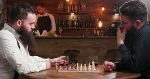 Οι αρσενικοί φίλοι με τις γενειάδες συναντήθηκαν σε έναν φραγμό για να παίξουν ένα παιχνίδι σκακιού απόθεμα βίντεο