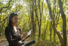 Οι γυναίκες παίρνουν τις σημειώσεις στο σημειωματάριο ενώ στον τρόπο στοκ εικόνα με δικαίωμα ελεύθερης χρήσης