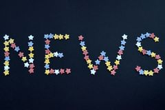 Οι ειδήσεις λέξης γράφονται στο λεπτό τύπο αστεριών ζύμης ζάχαρης σε ένα μαύρο υπόβαθρο, για τη διαφήμιση, εμπόριο, πωλήσεις στοκ φωτογραφία