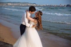 Οι εραστές newlyweds εξετάζουν ο ένας τον άλλον και ξοδεύουν το χρόνο μαζί στην ωκεάνια παραλία στοκ φωτογραφίες