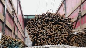 Οι εργαζόμενοι που χρησιμοποιούν έναν γερανό ξεφορτώνουν μια δέσμη των ράβδων χάλυβα απόθεμα βίντεο