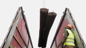 Οι εργαζόμενοι που χρησιμοποιούν έναν γερανό ξεφορτώνουν μια δέσμη των ράβδων χάλυβα φιλμ μικρού μήκους