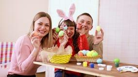 Οι εύθυμοι γονείς με την κόρη της, καταδεικνύουν στη κάμερα τους εργασία-συγκεκριμένα, αυγά ενός τα φωτεινά και ζωηρόχρωμα Πάσχας απόθεμα βίντεο