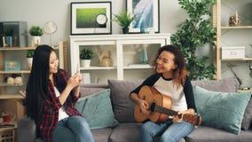 Οι θηλυκοί φίλοι έχουν τη διασκέδαση στο σπίτι, το κορίτσι αφροαμερικάνων παίζει την κιθάρα και η ασιατική νέα γυναίκα καταγράφει απόθεμα βίντεο