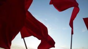 Οι κόκκινες σημαίες κυματίζουν ενάντια στο μπλε ουρανό απόθεμα βίντεο