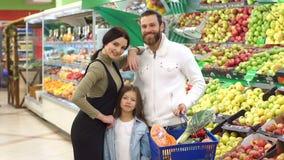 Οι νέοι γονείς με μια μικρή κόρη επιλέγουν τα φρέσκα μήλα σε μια μεγάλη υπεραγορά απόθεμα βίντεο