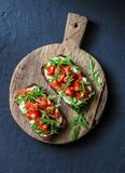 Οι ντομάτες και ολόκληρο το σιτάρι σαλάτας πυραύλων πασπαλίζουν το bruschetta σε έναν ξύλινο τεμαχίζοντας πίνακα σε ένα σκοτεινό  στοκ εικόνες