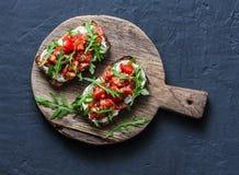 Οι ντομάτες και ολόκληρο το σιτάρι σαλάτας πυραύλων πασπαλίζουν το bruschetta σε έναν ξύλινο τεμαχίζοντας πίνακα σε ένα σκοτεινό  στοκ εικόνες με δικαίωμα ελεύθερης χρήσης