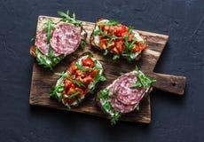 Οι ντομάτες, το ιταλικό λουκάνικο και ολόκληρο το σιτάρι σαλάτας πυραύλων πασπαλίζουν το bruschetta σε έναν ξύλινο τεμαχίζοντας π στοκ εικόνα