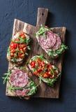Οι ντομάτες, το ιταλικό λουκάνικο και ολόκληρο το σιτάρι σαλάτας πυραύλων πασπαλίζουν το bruschetta σε έναν ξύλινο τεμαχίζοντας π στοκ εικόνες