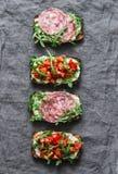 Οι ντομάτες, το ιταλικό λουκάνικο και ολόκληρο το σιτάρι σαλάτας πυραύλων πασπαλίζουν τα σάντουιτς σε ένα γκρίζο υπόβαθρο, τοπ άπ στοκ εικόνα με δικαίωμα ελεύθερης χρήσης