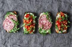 Οι ντομάτες, το ιταλικό λουκάνικο και ολόκληρο το σιτάρι σαλάτας πυραύλων πασπαλίζουν τα σάντουιτς σε ένα γκρίζο υπόβαθρο, τοπ άπ στοκ εικόνες