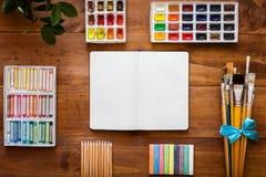 Οι δημιουργικές βοηθητικές προμήθειες εργασίας τέχνης θέτουν, ανοικτό σημειωματάριο για το σκίτσο, βούρτσες χρωμάτων, κουτί χρωμά στοκ εικόνες