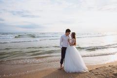 Οι όμορφες νεολαίες ακριβώς το ζεύγος που στέκεται στην ωκεάνια παραλία Το Newlyweds ξοδεύει το χρόνο μαζί, αγκαλιάζει και φιλά στοκ εικόνες