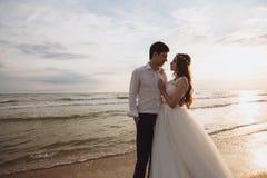 Οι όμορφες νεολαίες ακριβώς το ζεύγος που στέκεται στην ωκεάνια παραλία Το Newlyweds ξοδεύει το χρόνο μαζί, αγκαλιάζει και φιλά στοκ φωτογραφίες