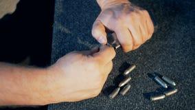Οι σκοπευτές βάζουν τις σφαίρες σε μια περίπτωση πυροβόλων όπλων, κλείνουν επάνω φιλμ μικρού μήκους