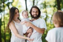 Οι συναρπαστικοί νέοι γονείς που ντύνονται στα άσπρα ενδύματα κρατούν την κόρη στα όπλα, την εξέταση το γιο και το χαμόγελο στοκ εικόνα με δικαίωμα ελεύθερης χρήσης