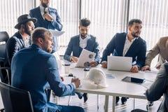 Οι τυπικά ντυμένοι άνδρες συνάδελφοι σε μια συνεδρίαση, κλείνουν επάνω στοκ φωτογραφία