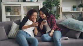 Οι χαμογελώντας νέες γυναίκες χρησιμοποιούν smartphones την ομιλία και την εξέταση γέλιου την οθόνη απολαμβάνοντας τα κοινωνικά μ φιλμ μικρού μήκους