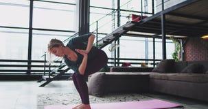 Οι χαρισματικές νέες ξανθές ασκήσεις γιόγκας γυναικείας άσκησης στο σπίτι στο καθιστικό, θέτουν σκληρά στη γιόγκα, αυτή που στέκε απόθεμα βίντεο