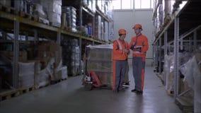 Οι υπάλληλοι πορτοκαλιούς σε workwear και τα κράνη που συζητούν την εργασία και κάνουν τις σημειώσεις μεταξύ των σειρών των ραφιώ απόθεμα βίντεο